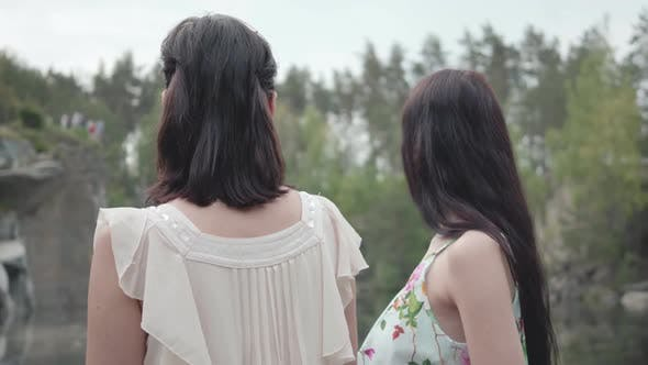 Thumbnail for Two Adorable Young Women Wear Summer Dresses Standing in the Top of Rock and Looking at Amazing View