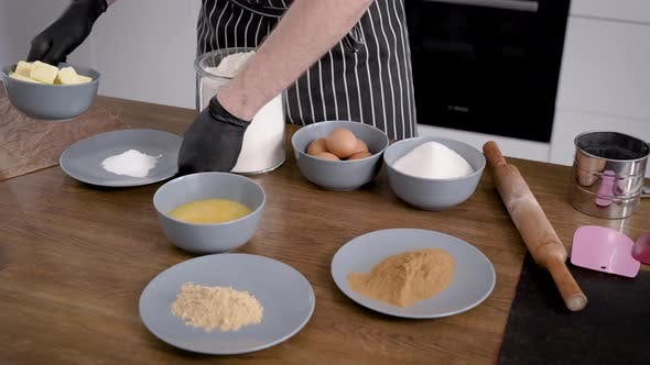 The Man Is a Cook in an Apron, His Hands in Gloves. On the Table Are the Ingredients for the Cupcake