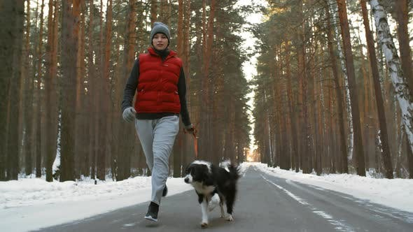 Thumbnail for Woman and Dog Running on Forest Road