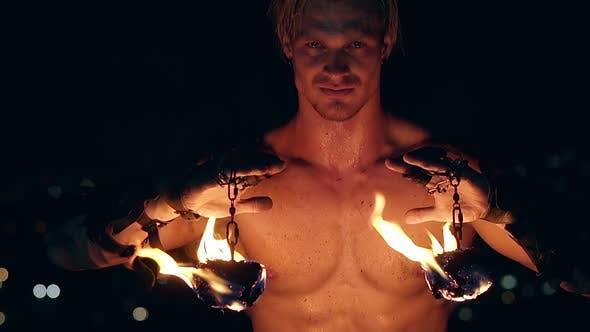 Jeune homme blond tient deux pois brûlants suspendus sur des chaînes. Ralenti. Gros plan