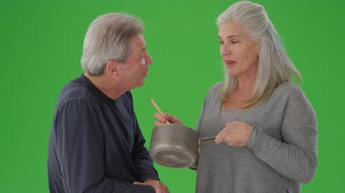 Charming senior white couple tasting cooking sauce