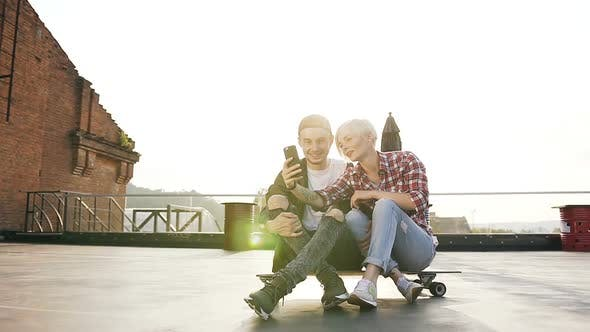 Cover Image for Young Hipster Couple are Sitting on Longboard Skateboard