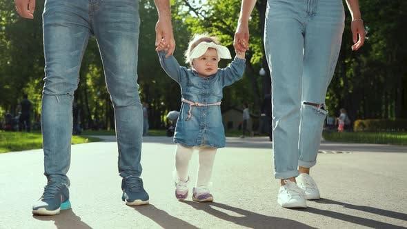 Eltern halten die Hände eines Kleinkind-Mädchens, das im Sommer im sonnigen Park mit Lens Flare-Effekt sp