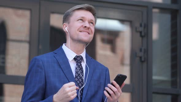 Thumbnail for Dancing Businessman Listening Music on Smartphone