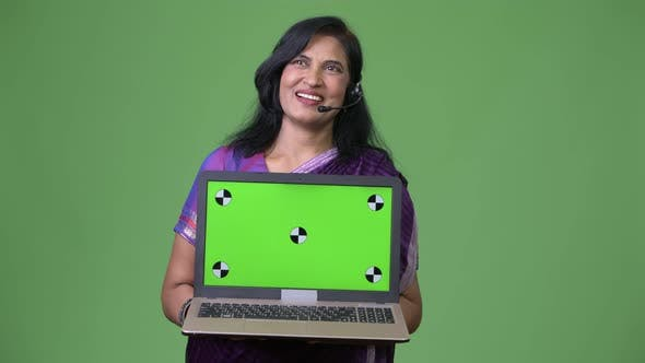 Thumbnail for Mature Happy Beautiful Indian Woman As Call Center Representative Thinking While Showing Laptop