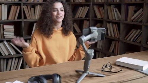 Hispanic Teen Girl Blogger Record Vlog Video Tutorial on Smartphone in Library