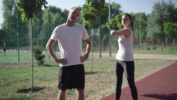 Thumbnail for Adult Caucasian Sportive People Warming Up Before Jogging on Running Track. Positive Slim Athletic