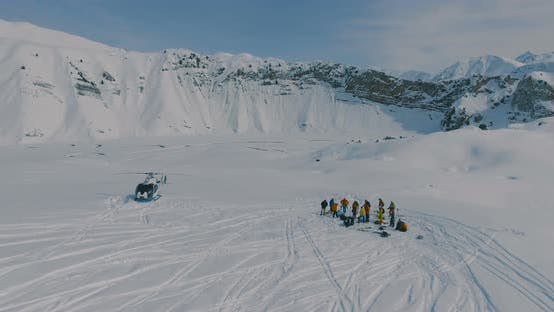 Cover Image for Heliskiing Helicopter and Group of Skiers, Snowboarders in the Winter Mountains