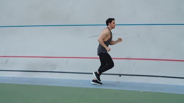 Thumbnail for Sport Man Running in Slow Motion on Track. Man Runner Jogging on Athletics Track
