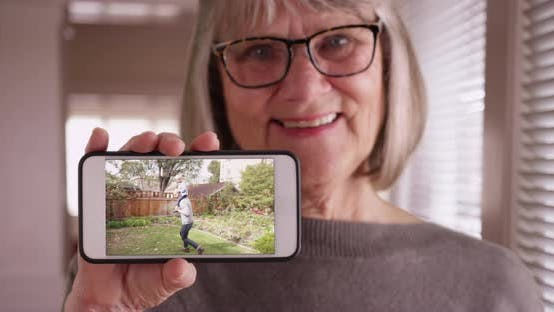 Thumbnail for Kind old lady showing smartphone footage of her family playing in backyard