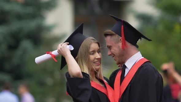 Thumbnail for Pretty Lady in Academic Dress Hugging Boyfriend and Smiling Graduation Party