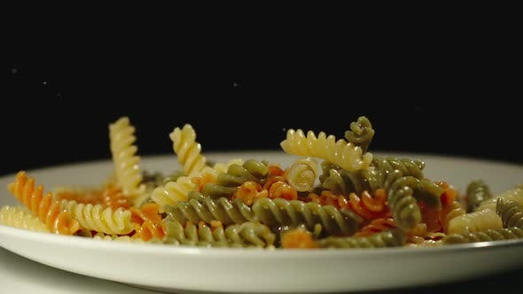 Thumbnail for SLOW MOTION: Cooked Color Spiral Pasta Fall Into Full Plate