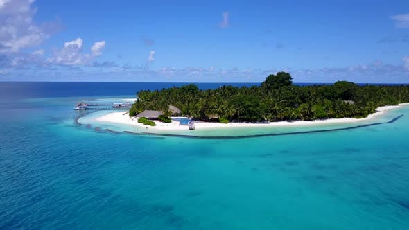 Wide angle aerial tourism shot of a white paradise beach and blue ocean background in colourful 4K