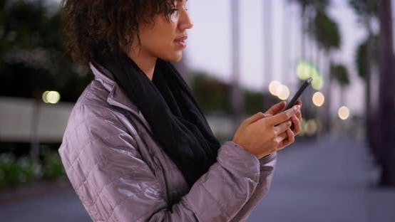 Thumbnail for Single black woman texting on smartphone outdoors, standing on sidewalk.