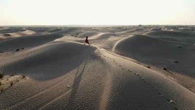 Aerial Footage of a Professional Dancer Performing in the Middle of a Desert