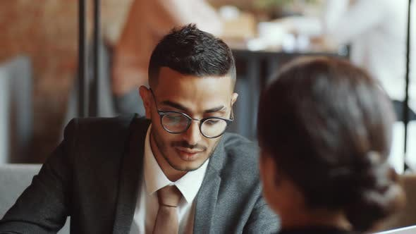 Thumbnail for Cheerful Arab Businessman Talking with Female Colleague in Cafe