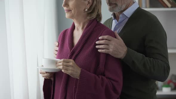 Thumbnail for Elderly Female with Cup of Tea by Window, Man Hugging Behind, Kissing on Cheek