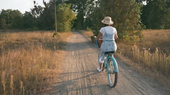 Thumbnail for Woman cyclist rides retro old bicycle in park green area.