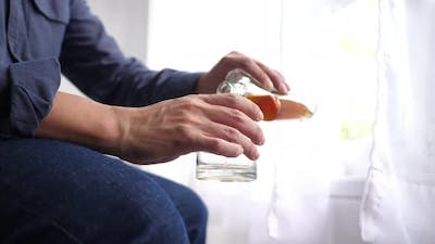 Alcoholic man with glass in hand pouring alcohol with tremors