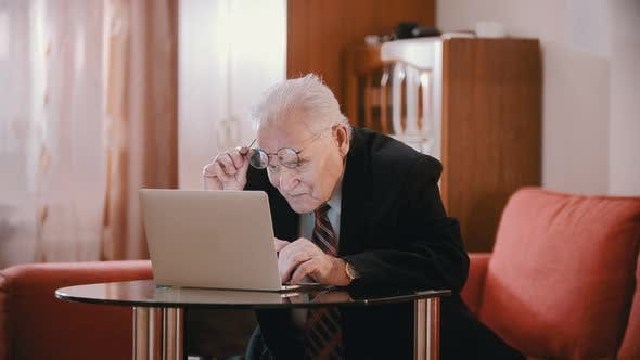 Thumbnail for Elderly Grandfather - Old Grandfather Is Putting on Glasses and Keeps Typing
