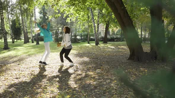 Thumbnail for Two Caucasian Women Tossing Yellow Leaves in the Autumn Park. Joyful Family Spending Sunny Day