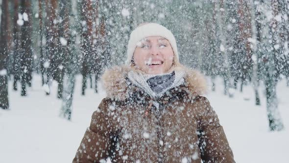 Beautiful Woman in Winter Clothes Throwing Snow Above Her Head and Smiling