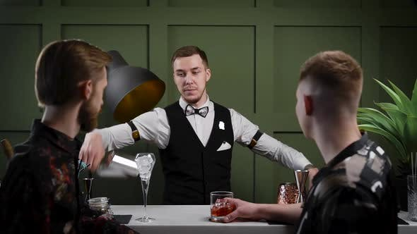 Thumbnail for A Male Bartender Prepares Cocktails. Two Friends of the Visitors Are Waiting for Their Drinks at the