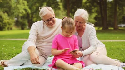 Grandparents and Granddaughter with Smartphone