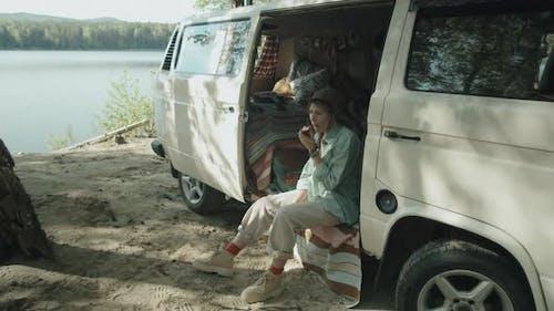 Female Tourist Eating Apple and Feeding Dog in Camper Van