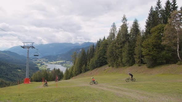 a Group of Adults and Children During a Bike Ride on Mountain Routes in the Alps