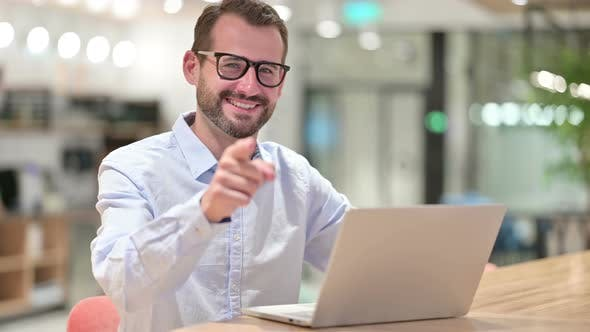 Thumbnail for Businessman with Laptop Pointing at the Camera in Office