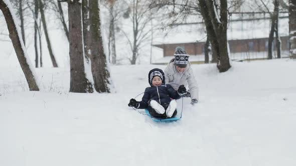 Kids Having Fun with Sledges on Snowy Hill