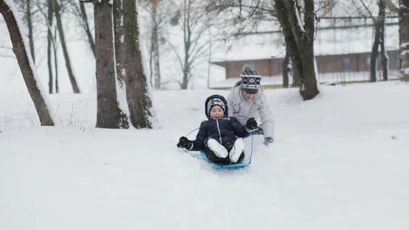 Kinder mit Spaß mit Schlitten auf Snowy Hill