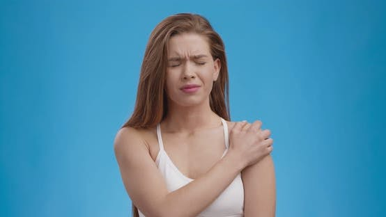 Thumbnail for Muscle Pain. Young Woman Suffering From Pain in Shoulder, Blue Studio Background, Slow Motion