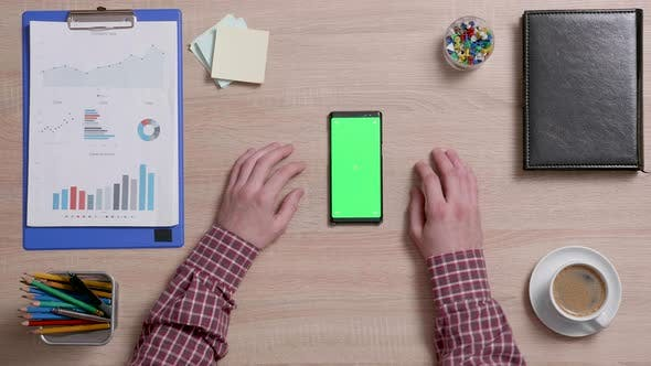 Thumbnail for Top View of Male Hands and a Smart Phone with Green Screen on a Wooden Office Desk