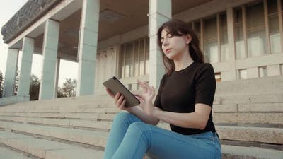 Young woman reads e-book