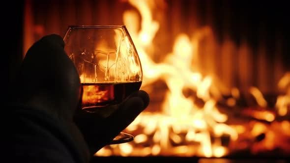 Thumbnail for Männliche Hand mit einem Glas Cognac auf dem Hintergrund des Kamins, Verkostung in einer gemütlichen Umgebung