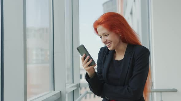 Thumbnail for Portrait of a Red-haired Woman Holding a Mobile Phone in Her Hand and Sincerely Smiling and