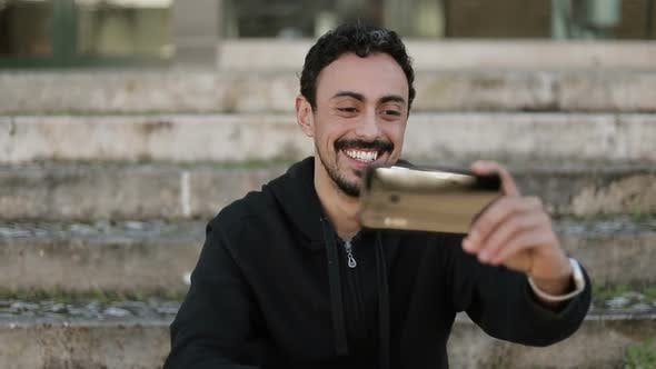 Thumbnail for Front View of Arabic Man Having Video Chat Outside, Waving Hand