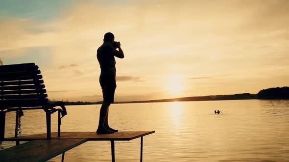 Fotograf fotografiert bei Sonnenuntergang eine Landschaft.