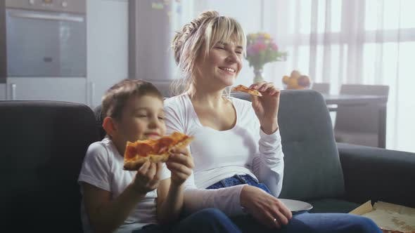 Cover Image for Family Watching Comic TV Show and Eating Pizza