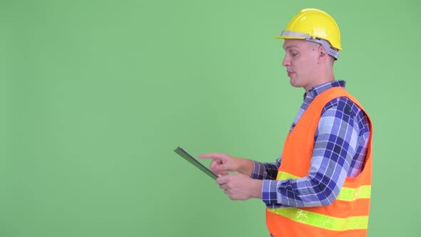 Thumbnail for Profile View of Happy Young Man Construction Worker Directing While Reading on Clipboard