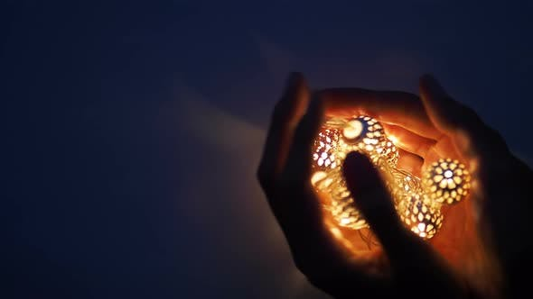 Thumbnail for Hands with Light Bulbs in Shape of Heart. Metal Light Bulbs with Delicate Pattern Shine in Dark