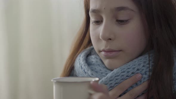 Cover Image for Portrait of Teenage Girl Wrapped in Warm Scarf Holding a Cup of Hot Tea in Hands. The Girl Feels Bad