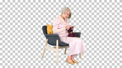 Elderly woman knitting sitting on a chair, Alpha Channel