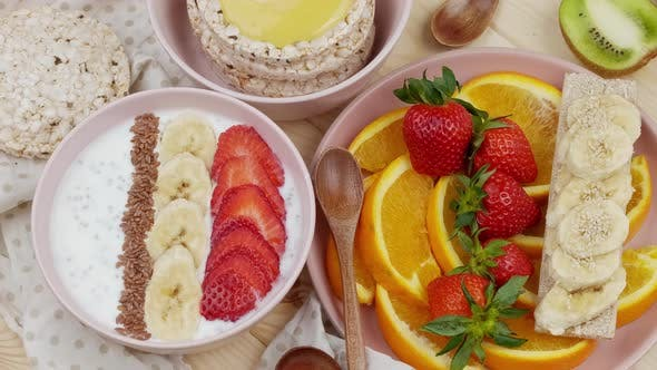 Morning Breakfast with Fruits Yoghurt with Bananas and Strawberries Honey Crisps Fresh Sliced Orange