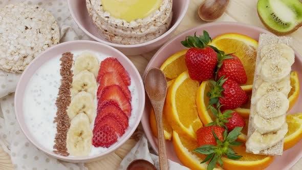 Morning Breakfast with Fruits Yoghurt with Bananas and Strawberries Honey Crisps Fresh Sliced Orange