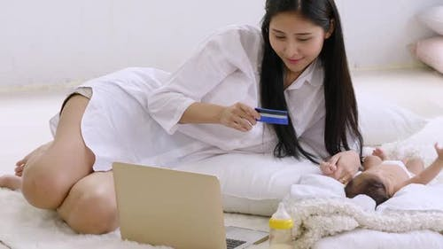 Beautiful young mother sitting with baby and shopping online on laptop at home