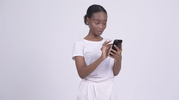 Thumbnail for Happy Young Beautiful African Woman Using Phone and Getting Good News