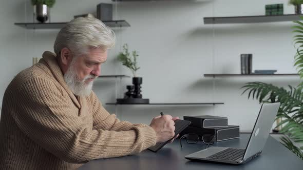 Thumbnail for An Elderly Man with a Gray Beard Draws with a Pen on a Tablet at Home in the Living Room